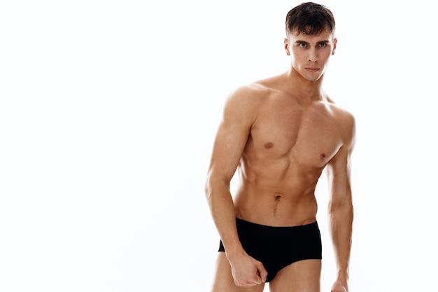 Sports man bodybuilder posing model muscles light background