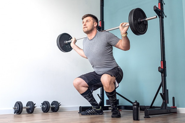 Sports man doing squats with barbell row at home in his small and bright apartment with minimalistic interior.