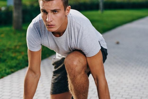 スニーカーのショートパンツと公園の屋外フィットネスで実行されているtシャツのスポーツマン。