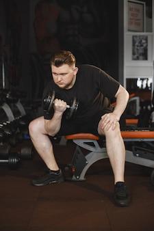 체육관에서 스포츠 남자입니다. 한 남자가 운동을 수행합니다. t- 셔츠에있는 남자