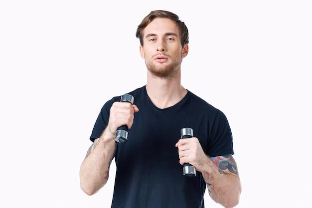 スポーツマンは、ダンベルを手に白い背景でフィットネスに取り組んでいます