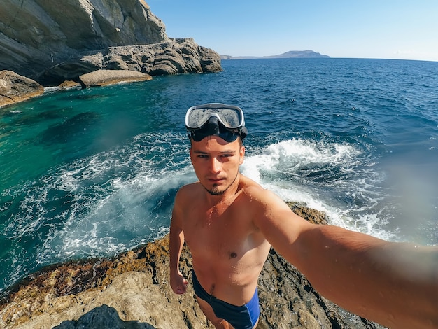 Sports the man in the mask for snorkelling taking a selfie