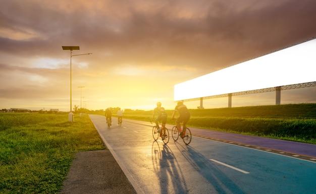 Спортсмен катается на велосипедах по дороге вечером возле пустого рекламного щита с закатным небом. летние упражнения на свежем воздухе для здоровой и счастливой жизни. велосипедист, езда на горном велосипеде на велосипедной дорожке.