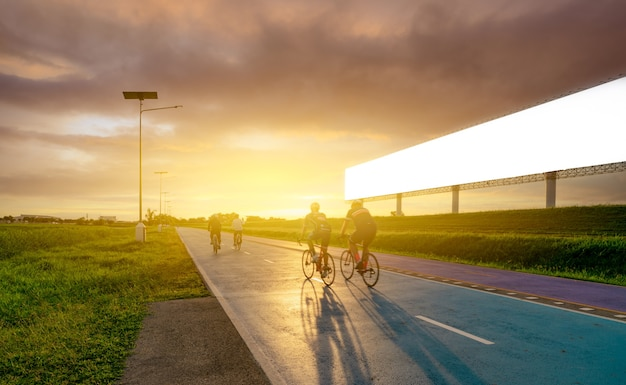 Sports man ride bicycles on the road in the evening near blank advertising billboard with sunset sky. summer outdoor exercise for healthy and happy life. cyclist riding mountain bike on bike lane.