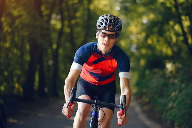 Sports man riding bike in summer forest