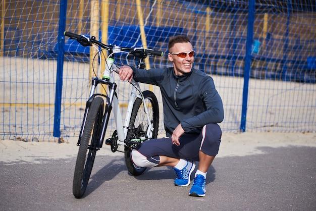 Sports man sitting next to the bike