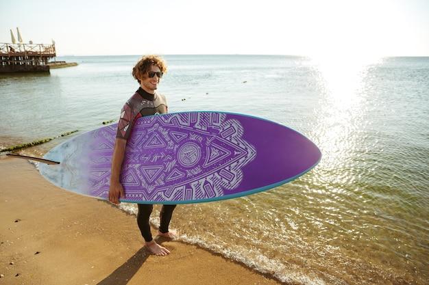 바다 해안에 걸쳐 그의 손에 서핑 보드와 함께 산책하는 스포츠 남자