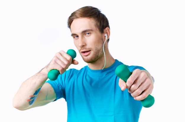 ヘッドフォンフィットネスエクササイズライトウォールで手にダンベルを持つスポーツ男