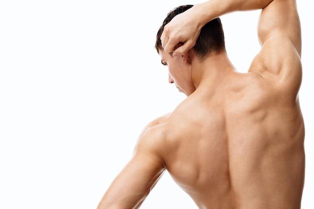 Спортивный мужчина с обнаженным торсом держит руку за голову и мышцы