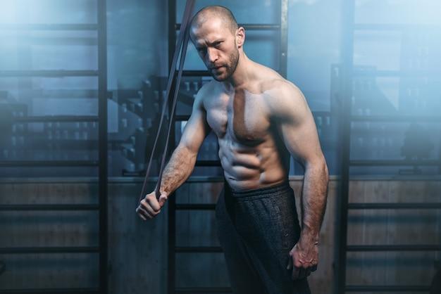 バンドで強力な上腕二頭筋運動を持つスポーツ男