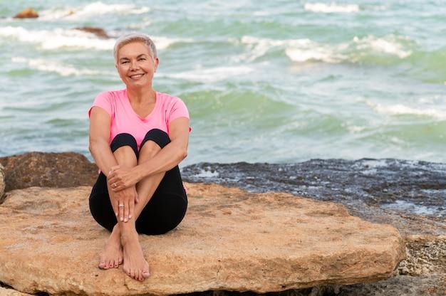 해변에 앉아 웃 고 스포츠 성숙한 여자.