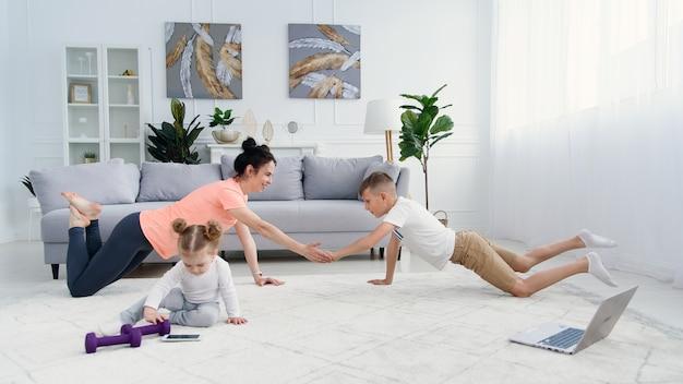 Спортивная мама с сыном делают утреннюю тренировку дома. мама и сын делают упражнения вместе, концепция здорового семейного образа жизни