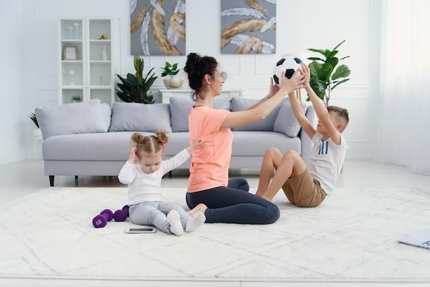 Спортивная мама с сыном делают утреннюю тренировку дома. мама и сын делают упражнения вместе, концепция здорового семейного образа жизни Premium Фотографии