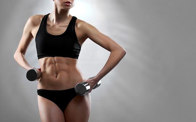 Спортивная мотивация обрезал студийный снимок великолепно подтянутой женщины, показывающей