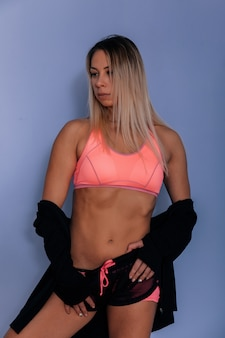 Sports muscular woman portrait wearing black sportswear over grey. attractive sexy caucasian woman with long blond hair in studio shot.