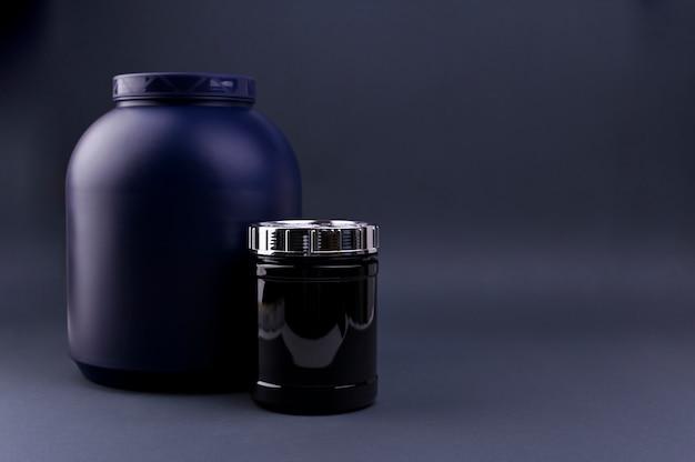 黒い背景に瓶にスポーツ栄養。カクテル用のプロテインパウダー。テキスト用の空きスペース。コピースペース、