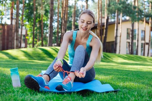 スポーツ衣装。トレーニングの準備をしながら靴をひもで締める素敵な若い女性