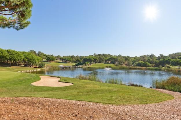 Спортивный парк для игры в гольф. с озером и фонтаном.