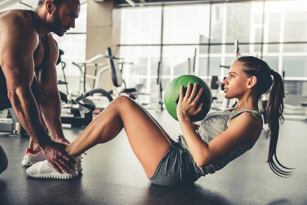 スポーツの人々はジムでフィットネスボールを使ってワークアウトしています。
