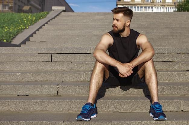 スポーツ、人、健康、活力、アクティブなライフスタイルのコンセプト。コンクリートの階段に座って、屋外でトレーニング中に休憩をとっている筋肉の日焼けした体を持つハンサムな若いひげを生やしたスポーツウーマンの写真