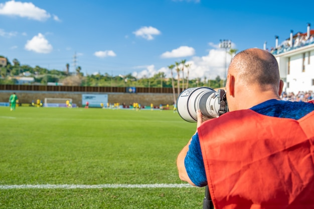 Sports photographers and journalists recorded during the game on the football field