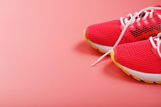 여유 공간이있는 분홍색 배경에 스포츠 핑크 스니커즈. 평면도, 최소한의 개념