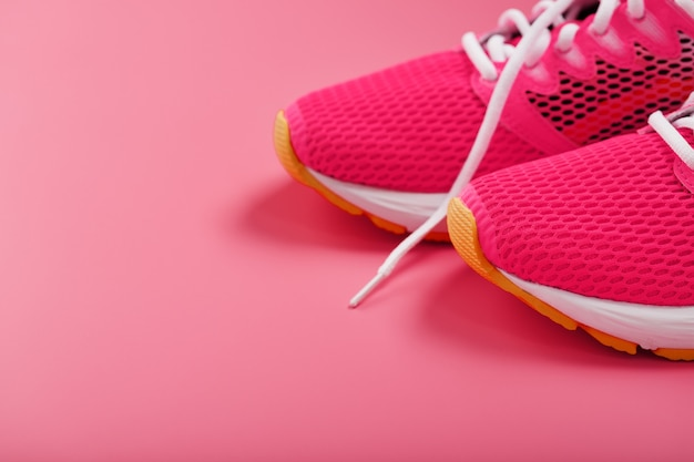Sports pink sneakers on a pink with free space.