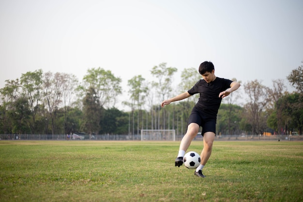 Sports and recreation concept a male soccer player wearing black t-shirt and pants practicing kicking the ball in the grassy field.