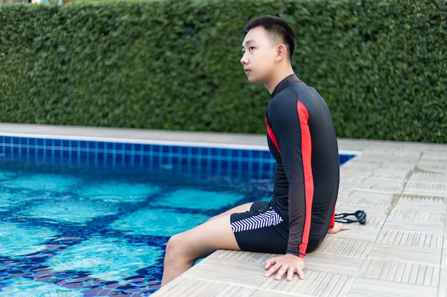 Sports and recreation concept a well-built boy sitting on the border of a blue-sky swimming pool enjoying the sunlight and lively weather.