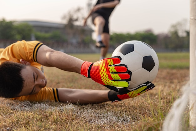 Sports and recreation concept a young male goalkeeper using his both hands catching the ball as preventing the opposing team from scoring.