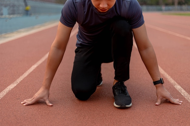 Sports and recreation concept a young male teenager wearing dark outfit in a preparing position before starting running on the running track.