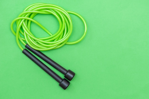 Sports rope for jumping green on a green background top view closeup the concept is a healthy lifestyle