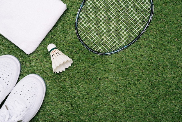 Спортивный комплект из синей спортивной обуви и воланов с ракеткой для бадминтона на фоне травы в концепции семейной деятельности