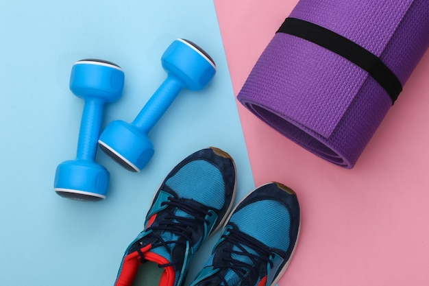 운동화(운동화)와 파란색 아령, 분홍색 파란색 배경에 피트니스 매트. 건강한 라이프 스타일, 피트니스 훈련. 평면도