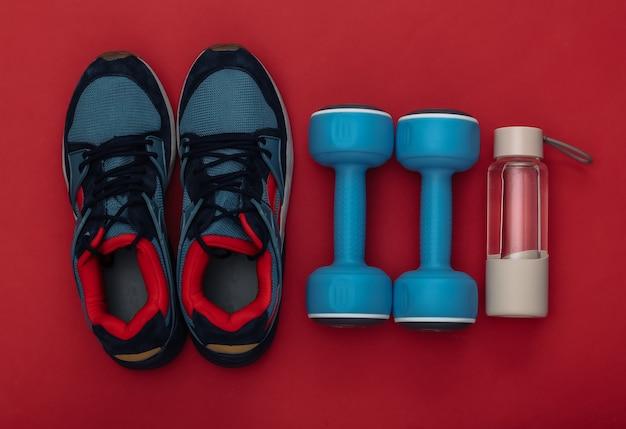スポーツシューズ(スニーカー)と青いダンベル、赤い背景に水筒。健康的なライフスタイル、フィットネストレーニング。上面図