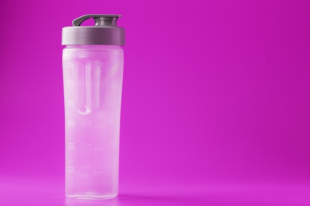 Sports smoothie bottle on pink surface