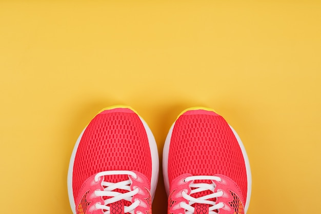 스포츠 운동화, 여유 공간이있는 노란색 배경에 분홍색. 평면도, 최소한의 개념
