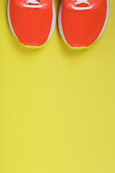 Sports sneakers, pink on a yellow surface with free space. top view, minimalistic concept