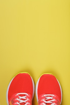 Sports sneakers, pink on a yellow with free space