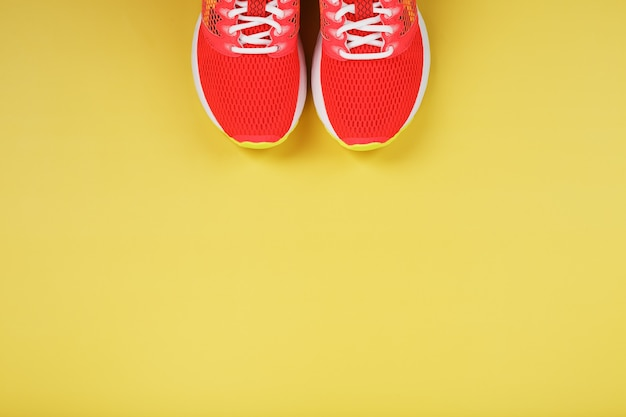 Sports sneakers, pink on a yellow with free space Premium Photo