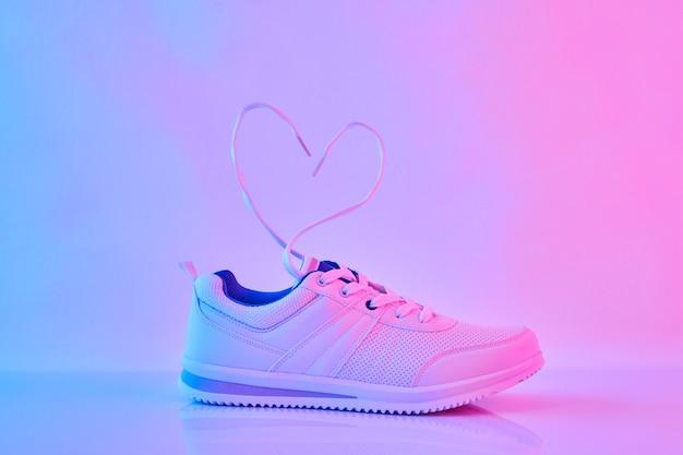 네온 불빛에 하트 모양의 끈이 달린 스포츠 스니커즈. 비행 신발 끈.