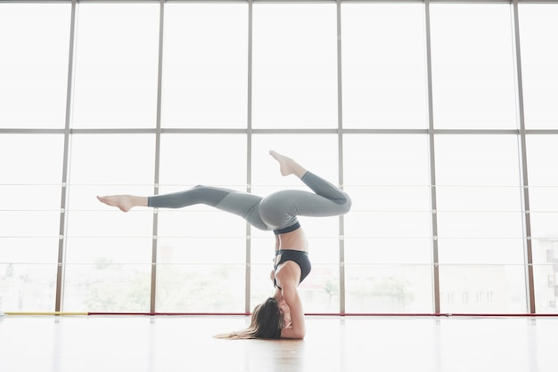 A sports sports woman who is doing yoga classes, stretching her legs near the big window