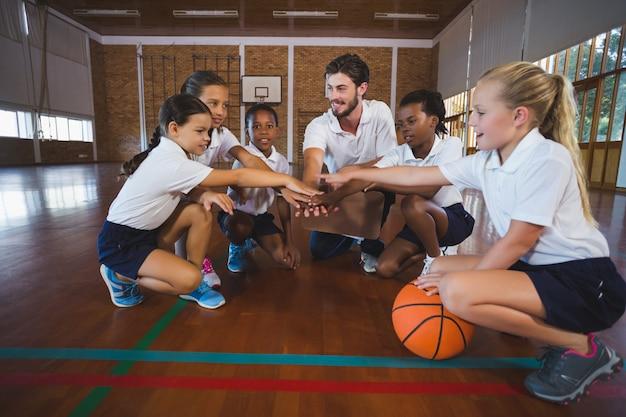 농구 코트에서 손 스택을 형성하는 스포츠 교사와 학교 아이들