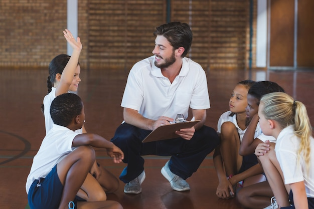 Sports teacher having discussion with his students