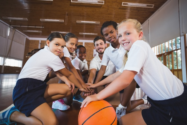 Sports teacher and school kids forming hand stack in basketball court