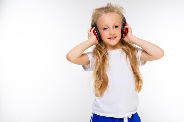 Спортивная девушка-подросток в спортивном костюме слушает музыку с большими красными наушниками на стене