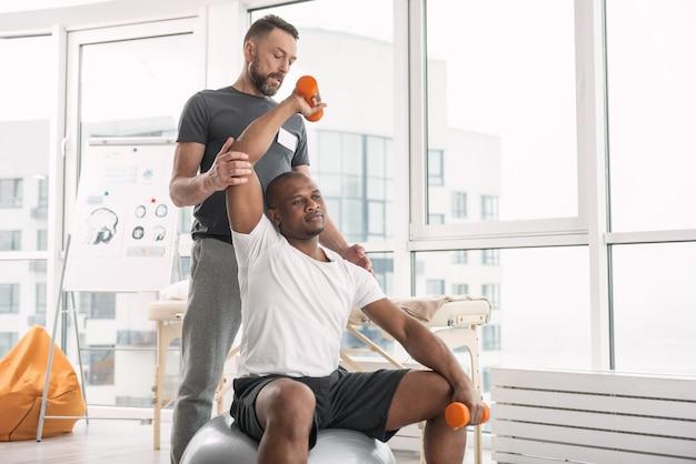 スポーツ療法。ジムにいる間ダンベルで運動する快適な格好良い男