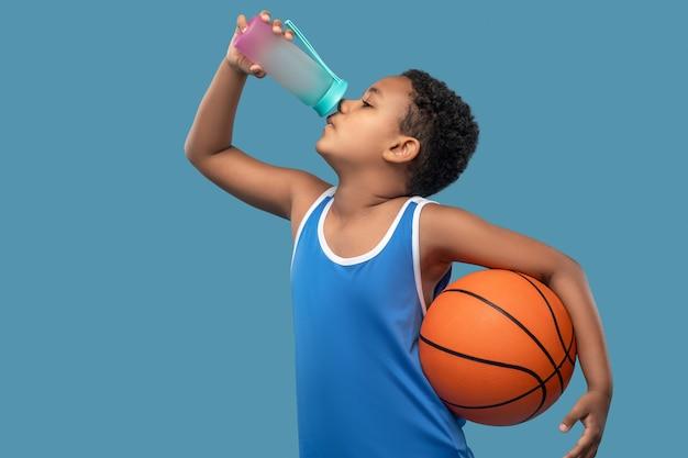 Спорт, жажда. темнокожий мальчик боком в синей рубашке с мячом, пьющим воду из спортивной бутылки