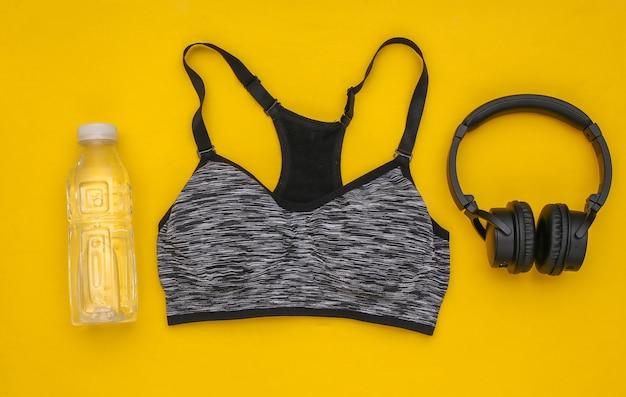黄色の背景にスポーツトップブラ、ボトルウォーター、ステレオヘッドフォン。スポーツとフィットネス。トレーニングの準備をしています。上面図。フラットレイ