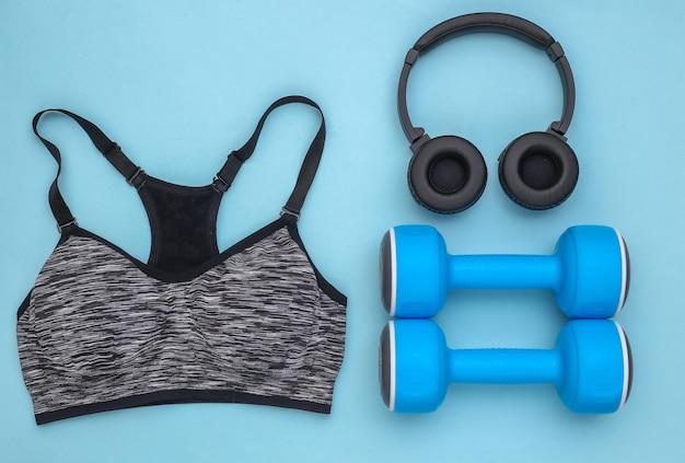 青い背景にスポーツトップブラ、ダンベル、ステレオヘッドフォン。スポーツとフィットネス。上面図。フラットレイ